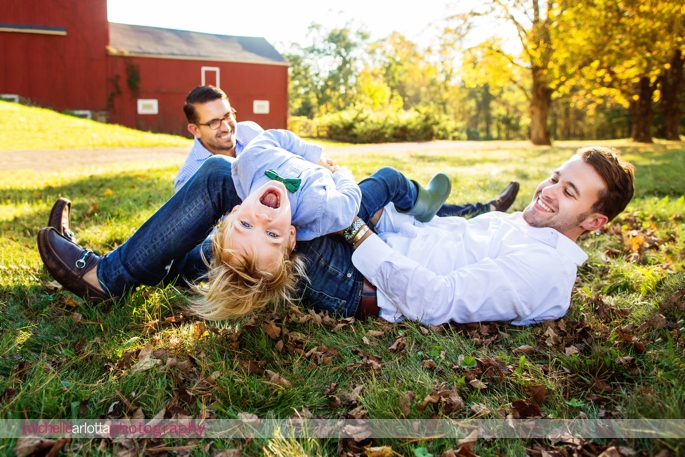 toddler plays around on his two dads like a jungle gym during candid family photography session in New Jersey