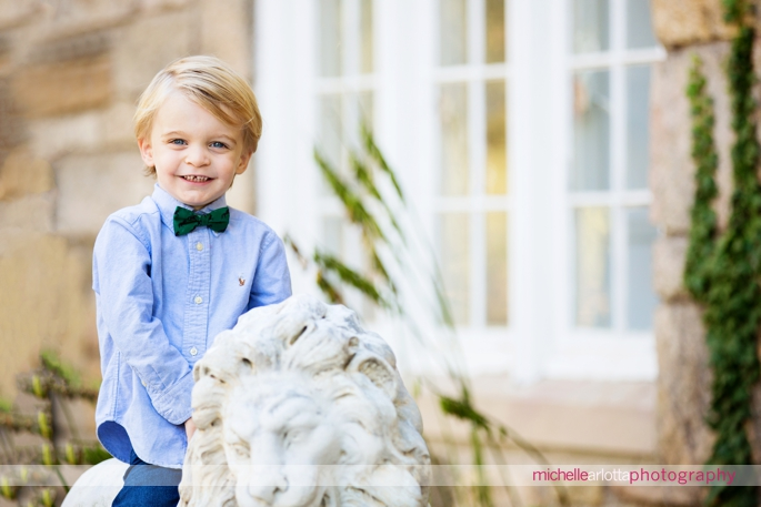toddler with bowtie smiles for the camera during family photography session in New Jersey