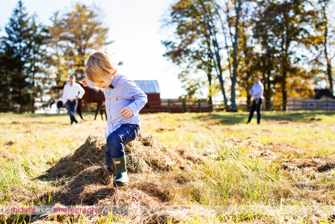 toddler with bowtie and hunter boots plays in the hay during photography session in Bedminster, New Jersey
