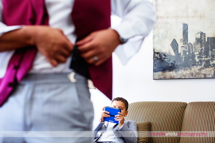ring bearer plays video games while groomsmen get dressed at battleground country club