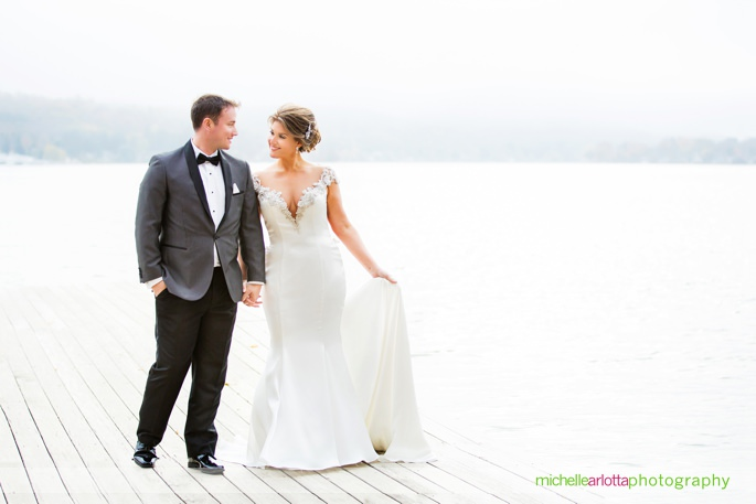 bride in jade bridal atelier wedding gown with groom in stylish suit hold hands on dock on lake mohawk in Sparta new jersey