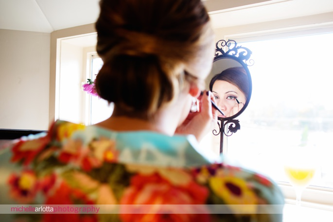 bridesmaid in floral robe does makeup in mirror at lake mohawk country club wedding nj