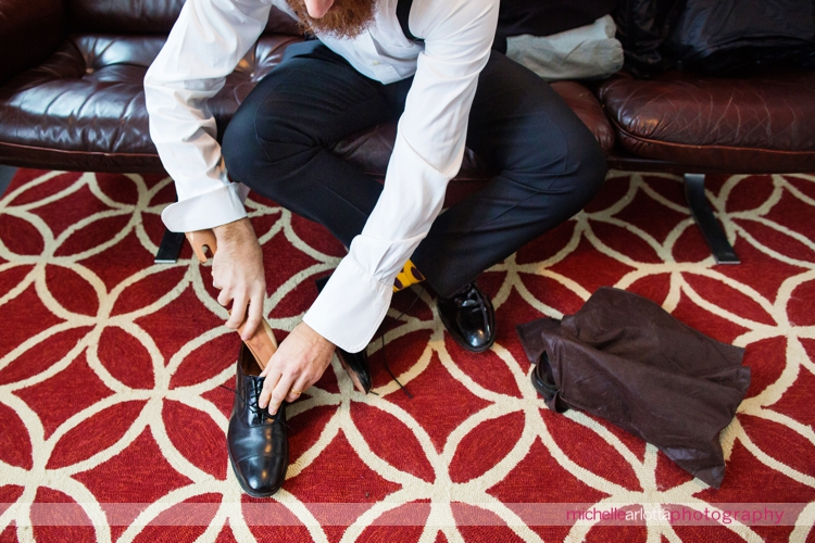 groomsmen puts on shoes in Pelham house