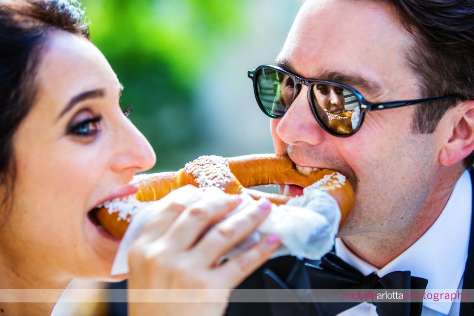 Liberty House summer wedding new jersey couple biting nyc pretzel at the same time